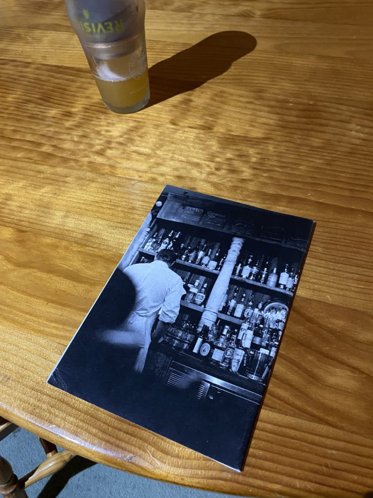 back cover of a zine on a blonde wood table - photograph of the front of a bar, with a bartender in white's back visible